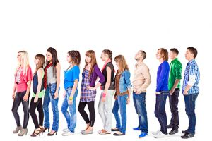 Large groupe of young adult people standing in a row and waiting for something. Studio shot on the white background.
